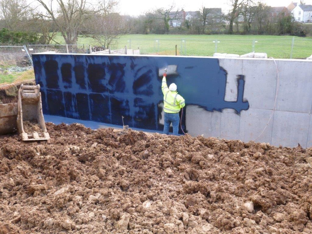 Spray Applied Liquid Membrane Applied to Concrete Retaining Wall as part of Waterproofing Installation.