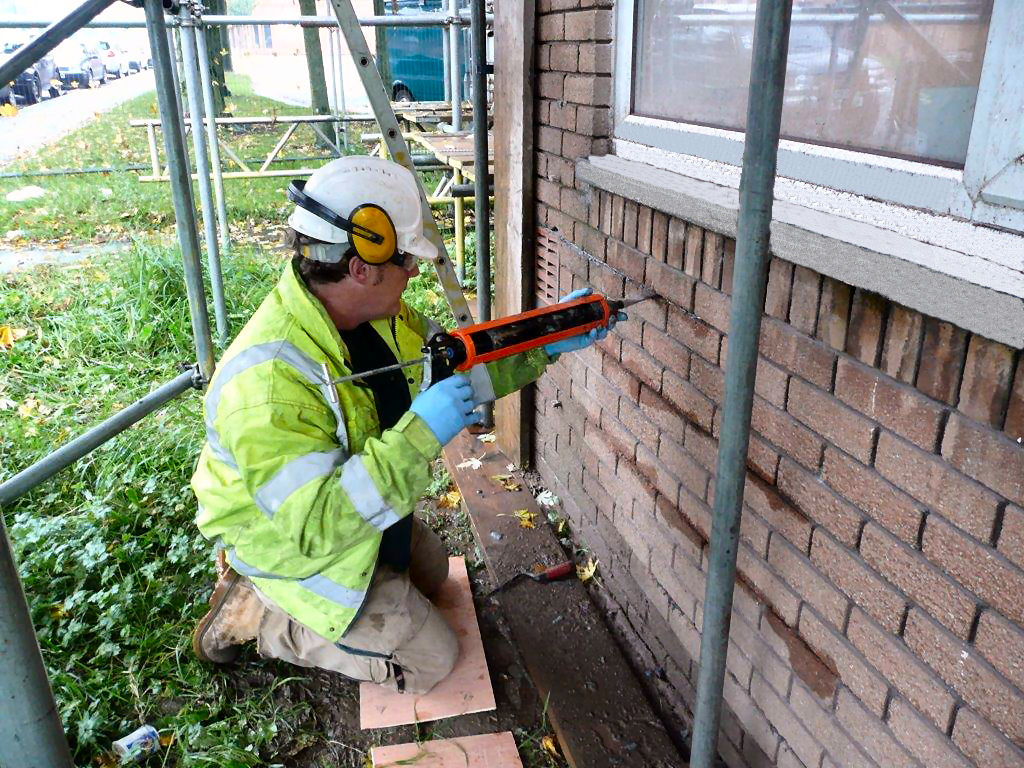 Protectahome Technician Inserting Grout for Helibar Installation